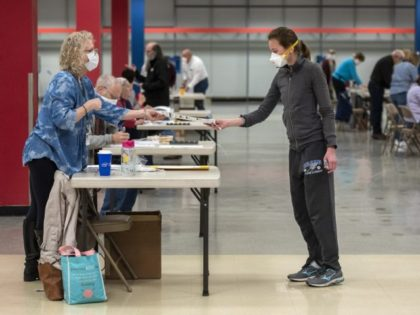 In this April 7, 2020 file photo, Bridget McDonald, right, receives a ballot from poll worker Patty Piek-Groth in Janesville, Wis. Only a handful of smaller Wisconsin municipalities are reporting a need for more poll workers, a positive sign as the coronavirus surges in the key battleground states just weeks …