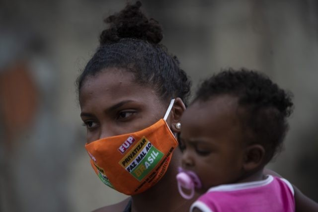 Carolaine Rocha, 22, holds her son while waiting to receive donated food from Petrobras workers and the oil workers union via the Tankers' Campaign that provide a supplement for the poor caught by declining wages and jobs due to the new coronavirus pandemic, in the Vila Vintem neighborhood of Rio …