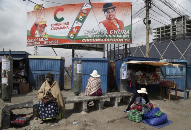 A billboard promoting presidential candidate Carlos Mesa of the Citizen Community political party towers over a trio of women in Rio Seco, Bolivia, Saturday, Oct. 17, 2020. Sunday's presidential election gives Bolivians a chance for a political reset as they struggle with the dramatic costs of the COVID-19 pandemic. (AP …