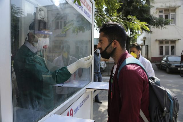 A health worker collects a nasal swab sample to test for COVID-19 at a government hospital in Jammu, India, Saturday, Oct. 17, 2020. The Health Ministry on Saturday reported 62,212 new cases in the past 24 hours, raising India's total to more than 7.4 million, second in the world behind …