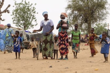 This June 4, 2020, file photo shows Women and children walk in a makeshift site for displaced people in Kongoussi, Burkina Faso. The U.N. humanitarian chief, Mark Lowcock, is hoping a major ministerial meeting on Tuesday, Oct. 20, 2020, will not only raise a billion dollars for the three countries …