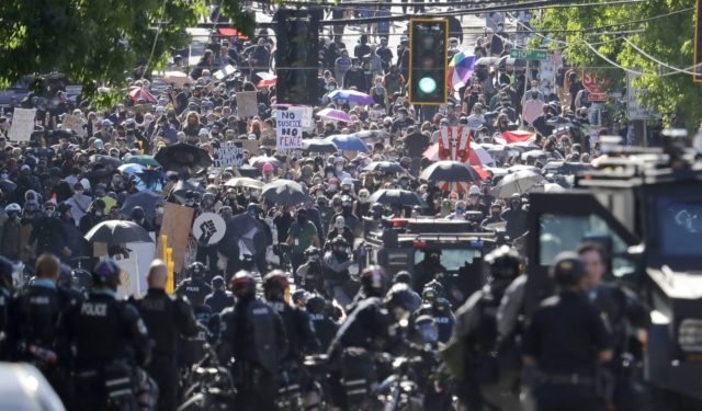 "In this July 25, 2020, file photo, police clash with protesters during a Black Lives Matter protest near the Seattle Police East Precinct headquarters in Seattle. New York, Seattle and Portland, three cities recently labeled ""anarchist jurisdictions"" by the U.S. Justice Department, are suing to to invalidate the designation and …"