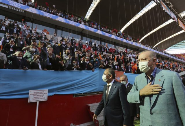 Turkey's President Recep Tayyip Erdogan, right, wearing a mask to help protect against the spread of coronavirus, greets his ruling party members gathered in a stadium, in Kayseri, Turkey, Saturday, Oct. 24, 2020. Turkey's Health Minister Fahrettin Koca said Friday COVID-19 infections were on the rise across the country and …