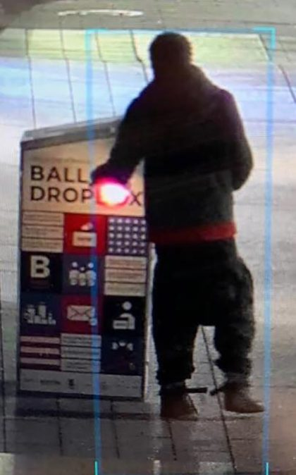 This surveillance image provided by the Boston Police Department shows a man approaching a ballot drop box outside the Boston Public Library, early Sunday, Oct. 25, 2020, in downtown Boston. Massachusetts election officials say a fire was set at the ballot drop box holding more than 120 ballots in what …