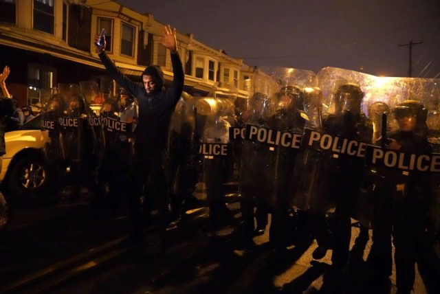 Sharif Proctor lifts his hands up in front of the police line during a protest in response to the police shooting of Walter Wallace Jr., Monday, Oct. 26, 2020, in Philadelphia. Police officers fatally shot the 27-year-old Black man during a confrontation Monday afternoon in West Philadelphia that quickly raised …
