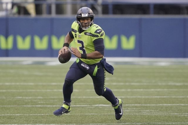 In this Oct. 11, 2020, file photo, Seattle Seahawks quarterback Russell Wilson looks for a receiver during the first half of the team's NFL football game against the Minnesota Vikings in Seattle. Wilson and his Grammy-winning wife, pop singer Ciara, are putting their money and celebrity behind rebranding a charter …