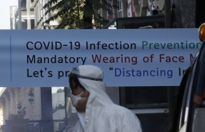A health official from the district office wearing protective gear, walks near a banner showing a precaution against the coronavirus in Seoul, South Korea, Thursday, Oct. 29, 2020. (AP Photo/Lee Jin-man)