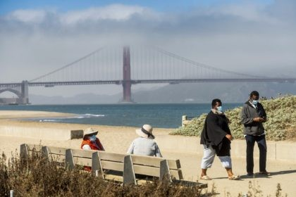 With the Golden Gate Bridge in the background, walkers wear masks while strolling at Crissy Field East Beach in San Francisco on Thursday, Oct. 22, 2020. As the coronavirus pandemic transforms San Francisco's workplace, legions of tech workers have left, able to work remotely from anywhere. Families have fled for …