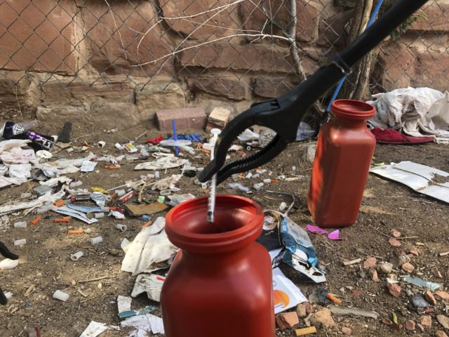 In this Aug. 9, 2019, file photo, a drug syringe found behind a vacant property in northeast Albuquerque, N.M., is placed into a container, as crews attempt to clear the lot of needles and other heroin paraphernalia. In what would be a first in the U.S., possession of small amounts …