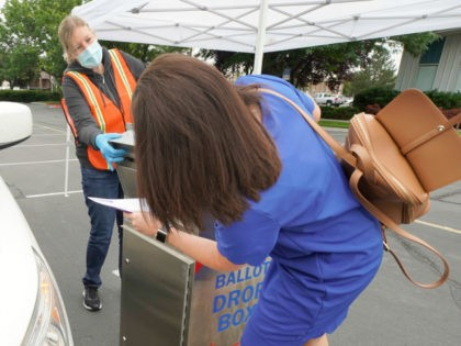A woman is helped by an election worker to put her ballot in a box while voting from her car in the parking lot of Lavell Edwards Stadium on the campus of Brigham Young University on June 30, 2020 in Provo, Utah. Mail-in ballots and drive-up voting has replaced in-person …