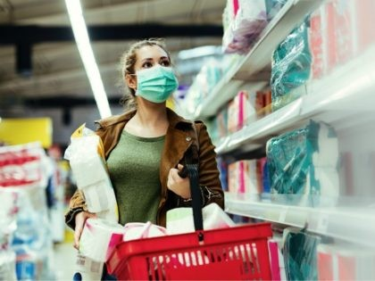 Young woman wearing face mask and making supplies of toilet paper while buying in supermarket in time of virus pandemic.