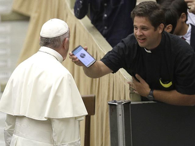 A priest shows Pope Francis a mobile phone before the start of the weekly general audience in the Paul VI Hall at the Vatican, Wednesday, Aug. 2, 2017. (AP Photo/Gregorio Borgia)