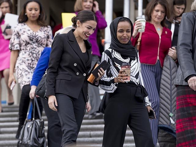 Rep. Alexandria Ocasio-Cortez, D-N.Y., center left, Rep. Ilhan Omar, D-Minn., center right, share a laugh as they walk down the House steps to take a group photograph of the House Democratic women members of the 116th Congress on the East Front Capitol Plaza on Capitol Hill in Washington, Friday, Jan. …