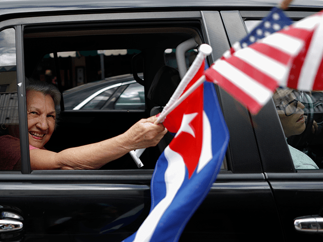 A woman waves American and Cuban flags as supporters of President Donald Trump drive in caravan down Calle Ocho in Little Havana, Miami, Saturday, Oct. 31, 2020. (AP Photo/Rebecca Blackwell)