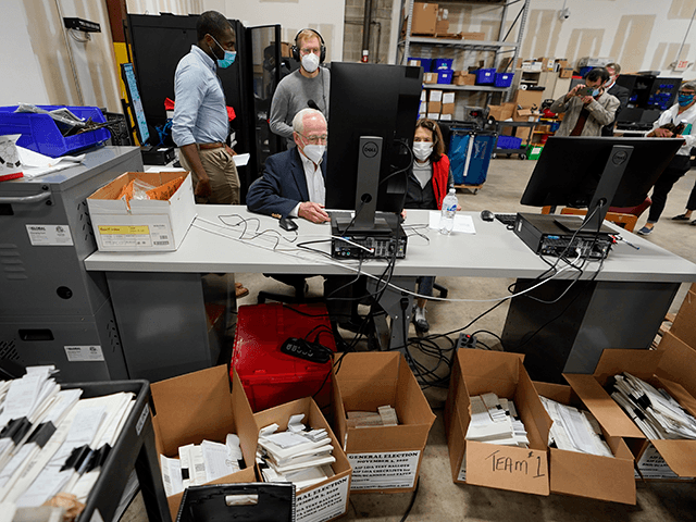 Democratic and Republican representatives review absentee ballots at the Fulton County Election preparation Center Wednesday, Nov. 4, 2020 in Atlanta. (AP Photo/John Bazemore)