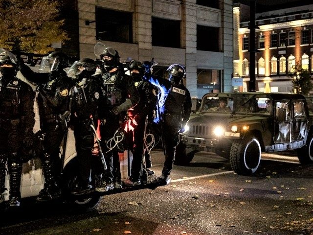 Police join the national guard during protests following the Nov. 3 presidential election in Portland, Or. Wednesday, Nov. 4, 2020. (AP Photo/Paula Bronstein)