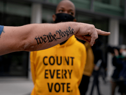 "The tattoo ""We The People"", a phrase from the United States Constitution, decorates the arm of Trump supporter Bob Lewis, left, as he argues with counter protestor Ralph Gaines while Trump supporters demonstrate against the election results outside the central counting board at the tcf Center in Detroit, Thursday, Nov. …"