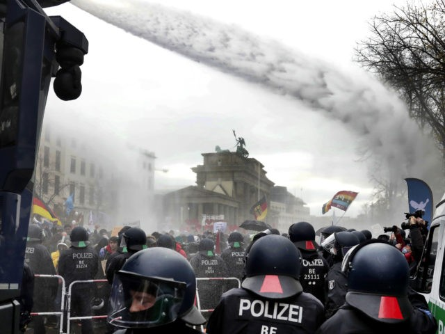 Police uses water canons to clear a blocked a road between the Brandenburg Gate and the Reichstag building, home of the German federal parliament, as people attend a protest rally in front of the Brandenburg Gate in Berlin, Germany, Wednesday, Nov. 18, 2020 against the coronavirus restrictions in Germany. Police …