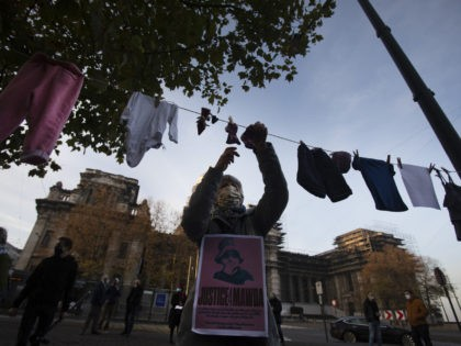 A woman hangs a piece of children's clothing on a line during a solidarity event for Mawda Shawri at the courthouse in Brussels, Monday, Nov. 23, 2020. A trial opened on Monday in the shooting death of two-year old toddler, Mawda Shawri, who was in a van during a high-speed …