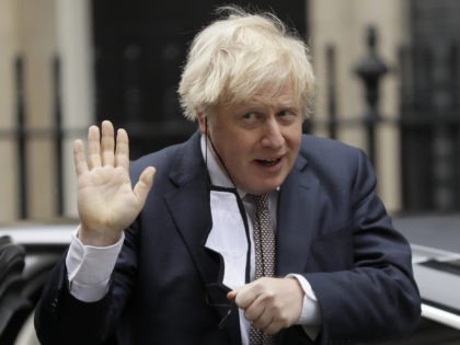 Britain's Prime Minister Boris Johnson takes his face mask off as he returns to10 Downing Street in London, Thursday, Nov. 26, 2020. Johnson leaves self-quarantine today after having close contact with a lawmaker who contracted the coronavirus in mid November. (AP Photo/Kirsty Wigglesworth)