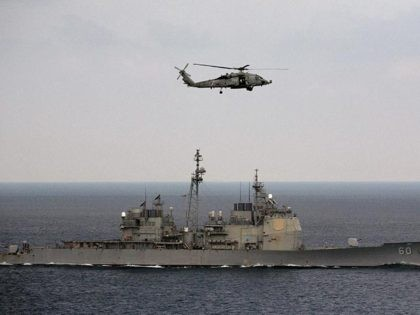 A U.S. Navy helicopter approaches to land on the deck of aircraft carrier USS Theodore Roosevelt (CVN 71), a missile cruiser and a nuclear-powered submarine, as the USS Normady sails in the Bay of Bengal during Exercise Malabar 2015, some 152 miles off eastern coast of Chennai, India, Saturday, Oct. …