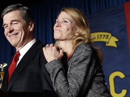 North Carolina Democratic candidate for governor Roy Cooper and his wife Kristin greet supporters during an election night rally in Raleigh, N.C., Wednesday, Nov. 9, 2016. The race between Cooper and Republican Gov. Pat McCrory remains too close to call. (AP Photo/Gerry Broome)