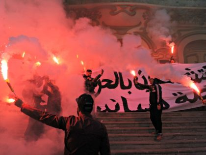 Tunisian protesters carry flares and shout slogans during celebrations in central Tunis on January 14, 2018, marking the seventh anniversary since the uprising that ousted ex-president Zine El Abidine Ben Ali and launched the Arab Spring. / AFP PHOTO / Anis MILI / The erroneous mention[s] appearing in the metadata …