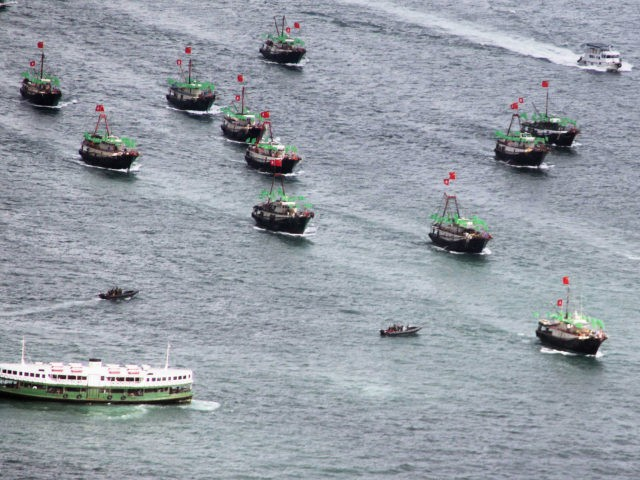 A flotilla of fishing boat bearing both the Chinese and Hong Kong flags sails past a Star Ferry (bottom-L) in Hong Kong on July 1, 2012 during celebrations to mark the 15th anniversary of the establishment of the Hong Kong Special Administrative Region (HKSAR). Hong Kong installed a new leader …