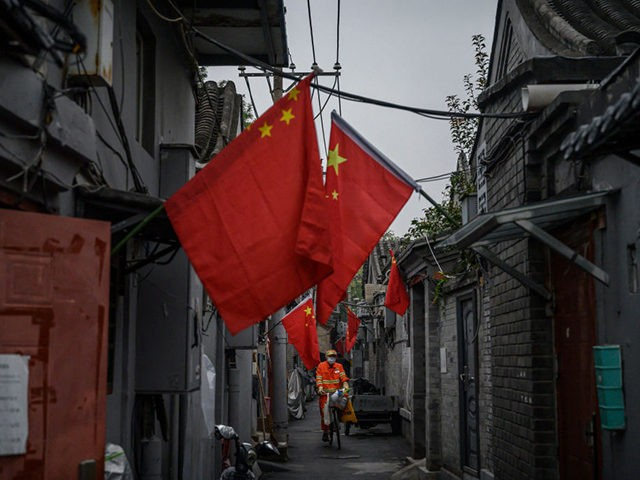 BEIJING, CHINA - OCTOBER 01: A Chinese worker wears a protective mask as he rides his bike in a small alleyway as national flags hang from buildings in a hutong neighbourhood on October 1, 2020 during the national holiday in Beijing, China. China is celebrating national day marking the 71st …