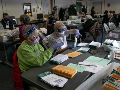 Election workers sort absentee ballot envelopes at the Lansing City Clerk's office on November 02, 2020 in Lansing, Michigan. For the first time, Michigan law is allowing clerks in Michigan cities to expedite the vote-counting process by removing secrecy envelopes from outer mailing envelopes one day ahead of the election. …