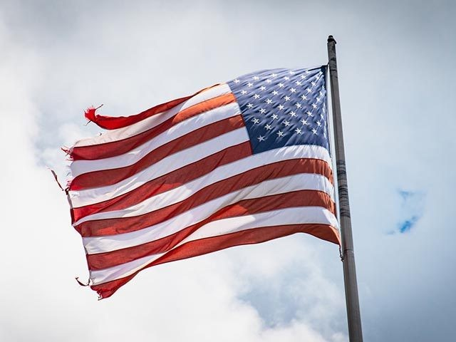 A visibly worn American flag waves in the wind.
