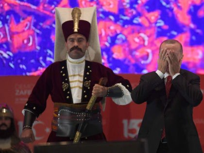 Turkish president Recep Tayyip Erdogan (R) prays next to a Turkish soldier wearing a ottoman uniform during a third anniversary commemoration rally at the Ataturk International Airport in Istanbul on July 15, 2019. - Turkey commemorates, on July 15, 2019 the third anniversary of a coup attempt which was followed …