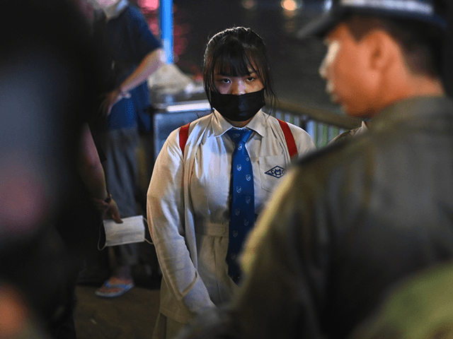 A high school student (C) is checked by police at a nearby rally to mark Taiwan's National Day, in the Tsim Sha Tsui district in Hong Kong on October 10, 2019. - Taiwan's National Day, also called called Double-Ten in a reference to the nationalist Republic of China set up …