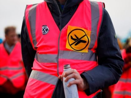An activist from climate action group Extinction Rebellion wears a 'no planes' patch as he listens to a speaker during protest against the building of a third runway at Heathrow Airport in west London on December 8, 2019. (Photo by Tolga Akmen / AFP) (Photo by TOLGA AKMEN/AFP via Getty …