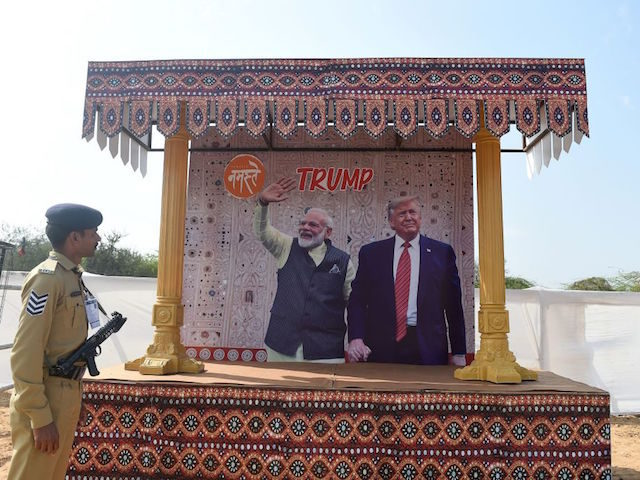 A police personnel from Gujarat Police Force looks at a billboard depicting India's Prime Minister Narendra Modi (C-L) and US President Donald Trump (C-R) in the Motera locality of Ahmedabad on February 23, 2020, in preparations ahead of Trump's first official visit to India. - Trade ties between the United …