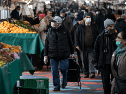 People wearing facemasks for protective measures do their grocery shopping at the Barbes Market, on March 18, 2020, in Paris, as a strict lockdown came into in effect in France to stop the spread of COVID-19, caused by the novel coronavirus. - A strict lockdown requiring most people in France …