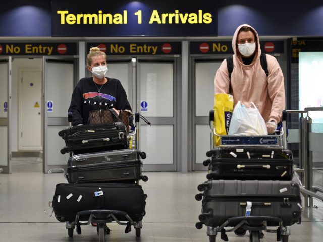 Passengers wearing PPE (personal protective equipment), including a face mask as a precautionary measure against COVID-19, arrive at Terminal 1 of Manchester Airport in northern England, on June 8, 2020, as the UK government's planned 14-day quarantine for international arrivals to limit the spread of the novel coronavirus begins. (Photo …