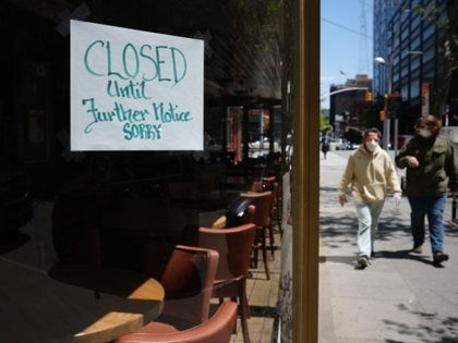 NEW YORK CITY- MAY 12: People walk through a shuttered business district in Brooklyn on May 12, 2020 in New York City. Across America, people are reeling from the loss of jobs and incomes as unemployment soars to historical levels following the COVID-19 outbreak. While some states are beginning to …