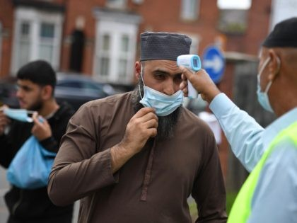 Worshippers wearing facemasks have their temperatures taken as they arrive for Friday prayers at Madina Masjid, Sheffield's central mosque, in Sheffield, northern England, on July 24, 2020 as a precaution against the spread of the novel coronavirus. - The Sheffield central mosque has taken a number of safety measures including …