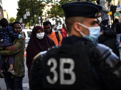 An asylum seeker family carrying a child stands next to riot police officers during their evacuation from a makeshift camp set along the Canal Saint-Denis in Aubervilliers near Paris early on July 29, 2020. (Photo by Christophe ARCHAMBAULT / AFP) (Photo by CHRISTOPHE ARCHAMBAULT/AFP via Getty Images)