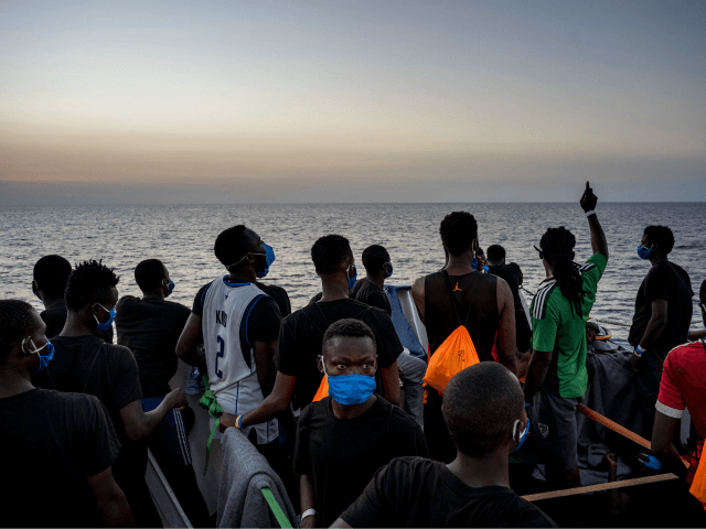 Migrants stand at sunset onboard the Sea-Watch 4 civil sea rescue ship react on sea off the coast of Sicily, Italy, on August 31, 2020. - More than 350 migrants are onboard the Sea-Watch 4, after it took more than 150 people from the German-flagged MV Louise Michel rescue vessel …