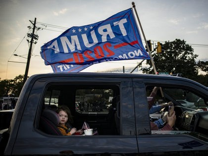 BETHESDA, MD - OCTOBER 04: A family waves a Trump campaign flag from their truck as they drive past Walter Reed National Military Medical Center after President Donald Trump was admitted for treatment of COVID-19 on October 4, 2020 in Bethesda, Maryland. The President announced via Twitter early Friday morning …
