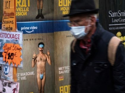 A man wearing a protective face mask walks past a shop selling masks as a poster of the film Borat by Sacha Baron Cohen is displayed in Paris,on the fourth day of a lockdown aimed at containing the spread of the novel coronavirus (Covid-19), on November 2, 2020. (Photo by …