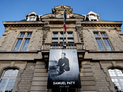 This picture taken on November 3, 2020 show a poster depicting French teacher Samuel Paty placed on the facade of the city hall in Conflans-Sainte-Honorine, 30kms northwest of Paris, on November 3, 2020, following the decapitation of the teacher on October 16. - France on November 2 honoured the teacher …