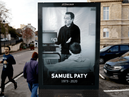 Pedestrians pass by a poster depicting French teacher Samuel Paty placed in the city center of Conflans-Sainte-Honorine, 30kms northwest of Paris, on November 3, 2020, following the decapitation of the teacher on October 16. - France on November 2 honoured the teacher beheaded near his school in Conflans-Sainte-Honorine by a …