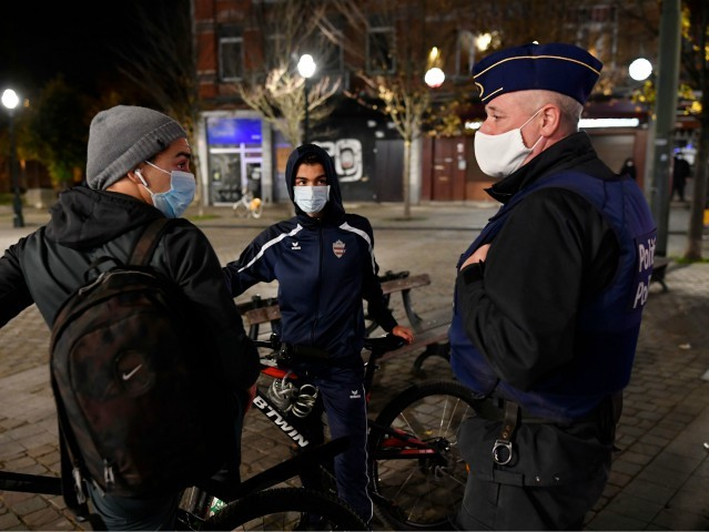 A police officer talks with teenagers during a patrol to control that people respect safety measures to contain the spread of Covid-19 outbreak due to the novel coronavirus in Brussels, Belgium, on November 03, 2020. (Photo by John THYS / AFP) (Photo by JOHN THYS/AFP via Getty Images)