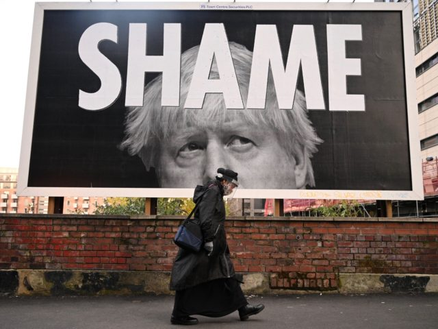 TOPSHOT - A woman wearing a protective face shield passes a billboard showing Britain's Prime Minister Boris Johnson in Manchester, north-west England on November 6, 2020, as the second lockdown comes into force in England. - A united effort to tackle spiking coronavirus infection rates has been called for as …