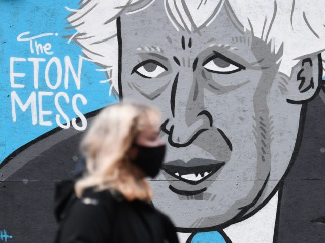 A woman wearing a mask because of the coronavirus pandemic walks past a mural depicting Britain's Prime Minister Boris Johnson on the front of a closed pub in Manchester, northwest England on November 10, 2020 during a second national coronavirus lockdown. (Photo by Oli SCARFF / AFP) (Photo by OLI …