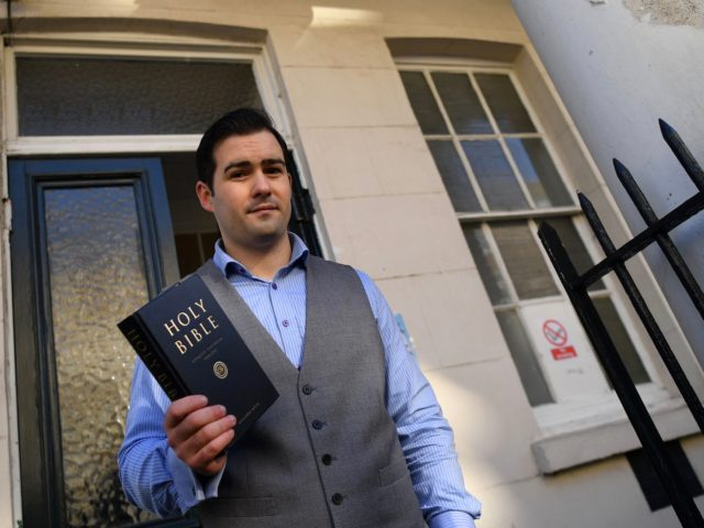 Pastor Regan King, of the Angel church in north London poses with a Holy Bible outside the church on November 15, 2020. - An evangelical church is defying lockdown restrictions to combat the spread of the novel coronavirus covid-19, by holding a public service on Sunday. (Photo by JUSTIN TALLIS …