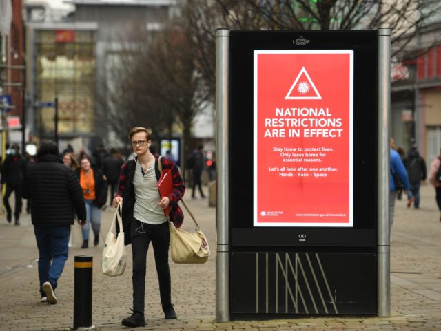 Pedestrians walk by a billboard displaying a Manchester City Council message about the about the national lockdown restrictions to combat the novel coronavirus pandemic in the centre of Manchester, northwest England, on November 26, 2020. - London will escape the tightest restrictions once England's national coronavirus lockdown ends next week, …